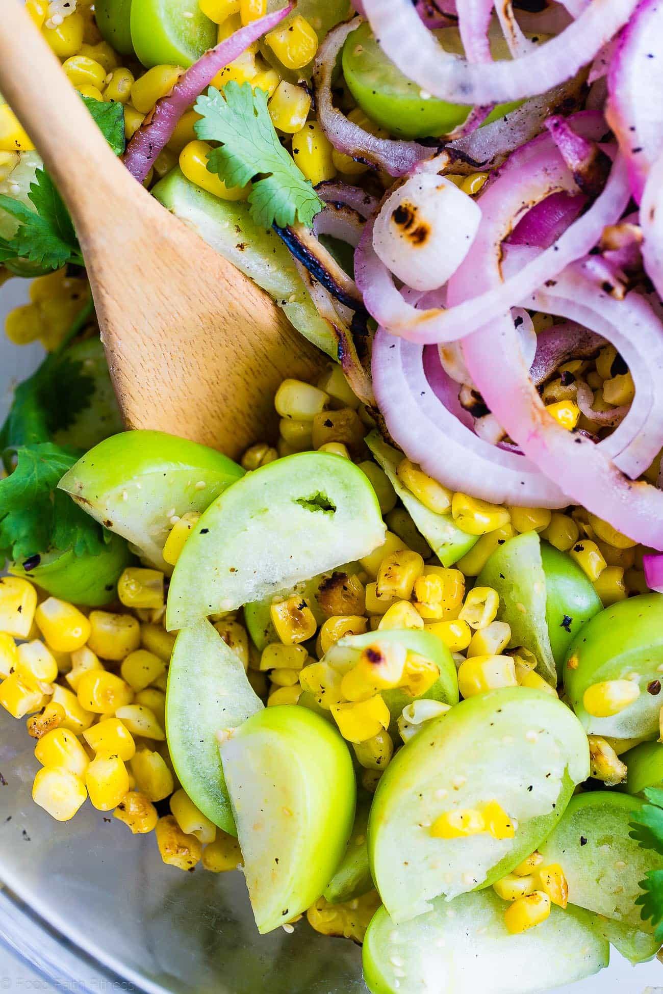 Close up shot of grilled corn and tomatillo salad. Recipe on Foodfaithfitness.com