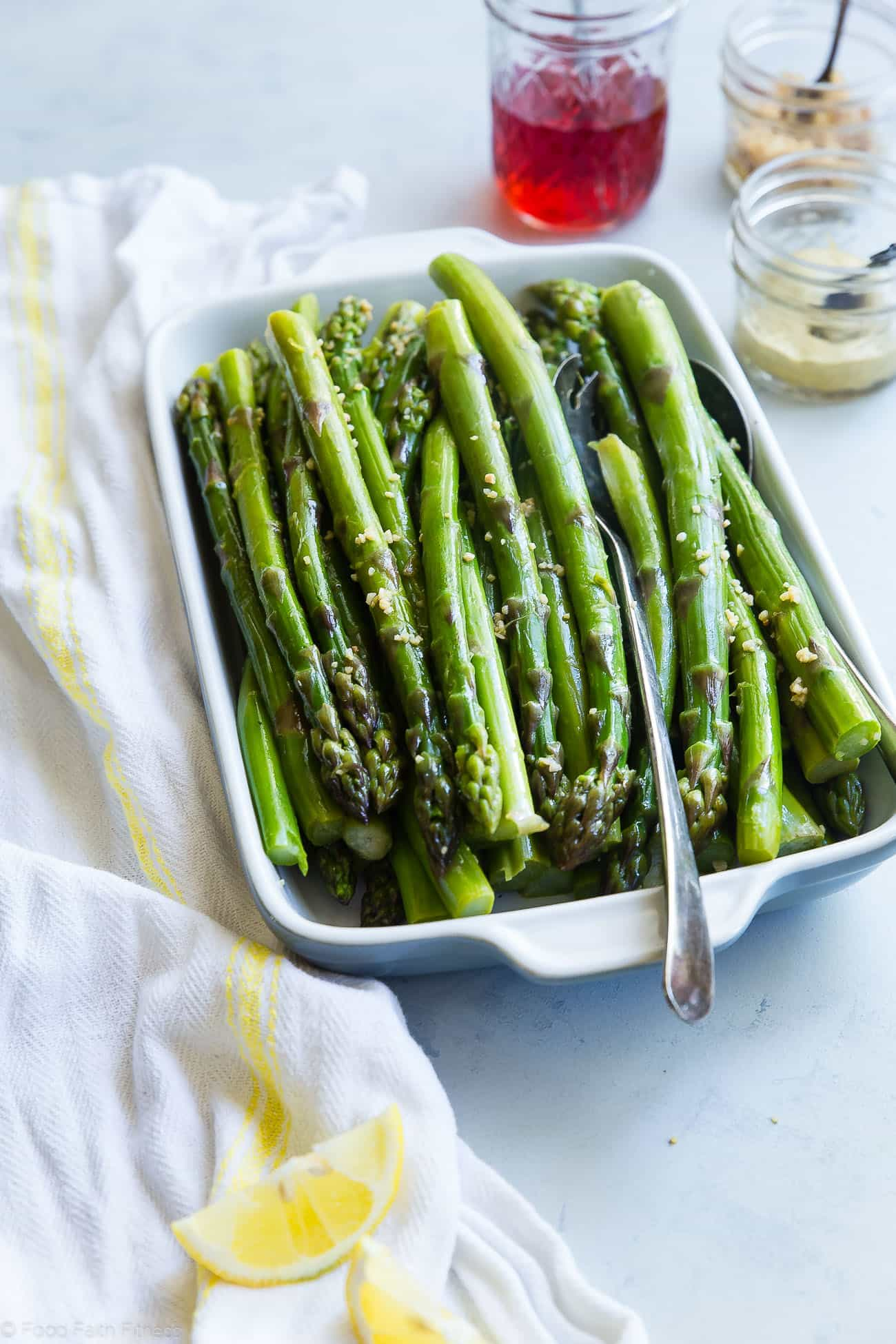 Blanched asparagus in a serving dish. Recipe on foodfaithfitness.com