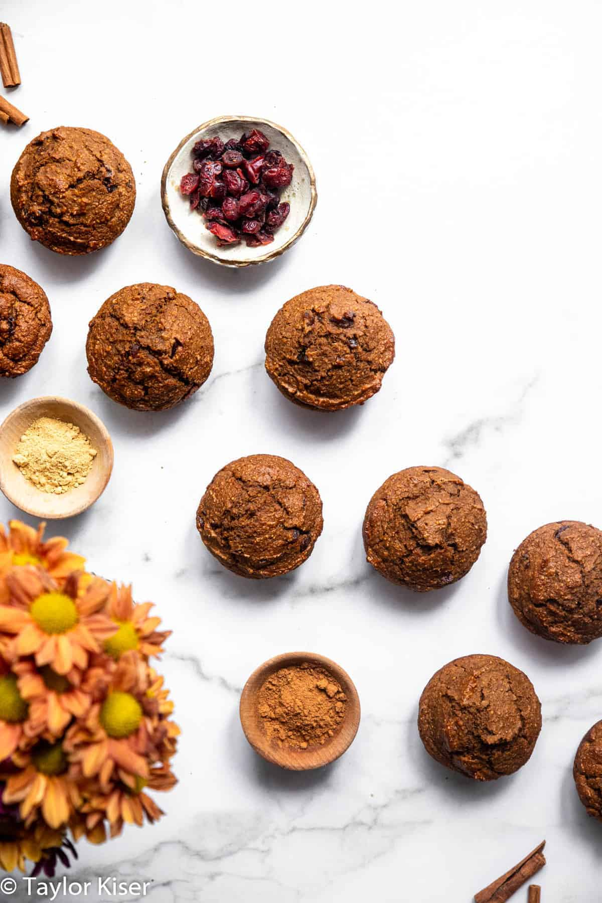 the tops of healthy pumpkin muffins on a table with flowers