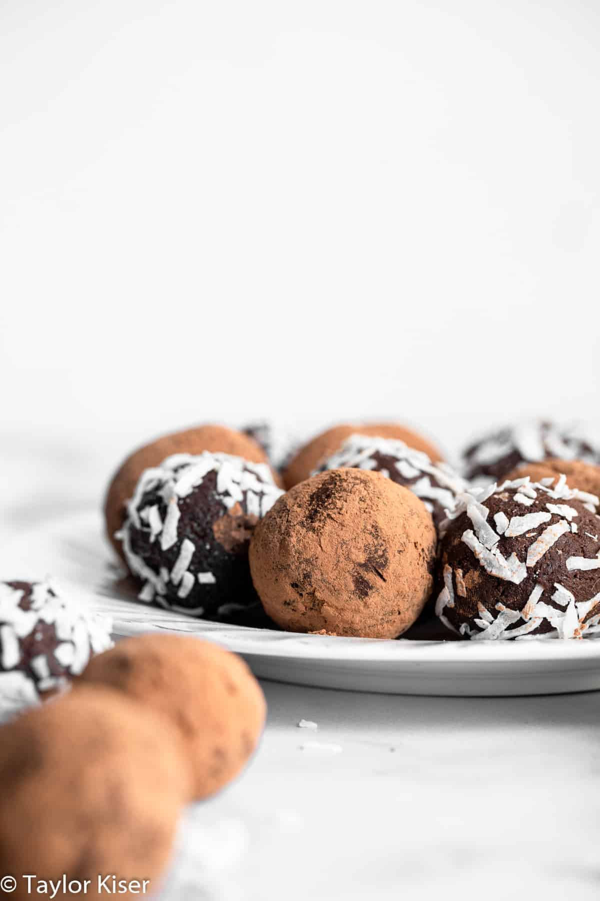 chocolate avocado truffles on a plate covered in cocoa powder
