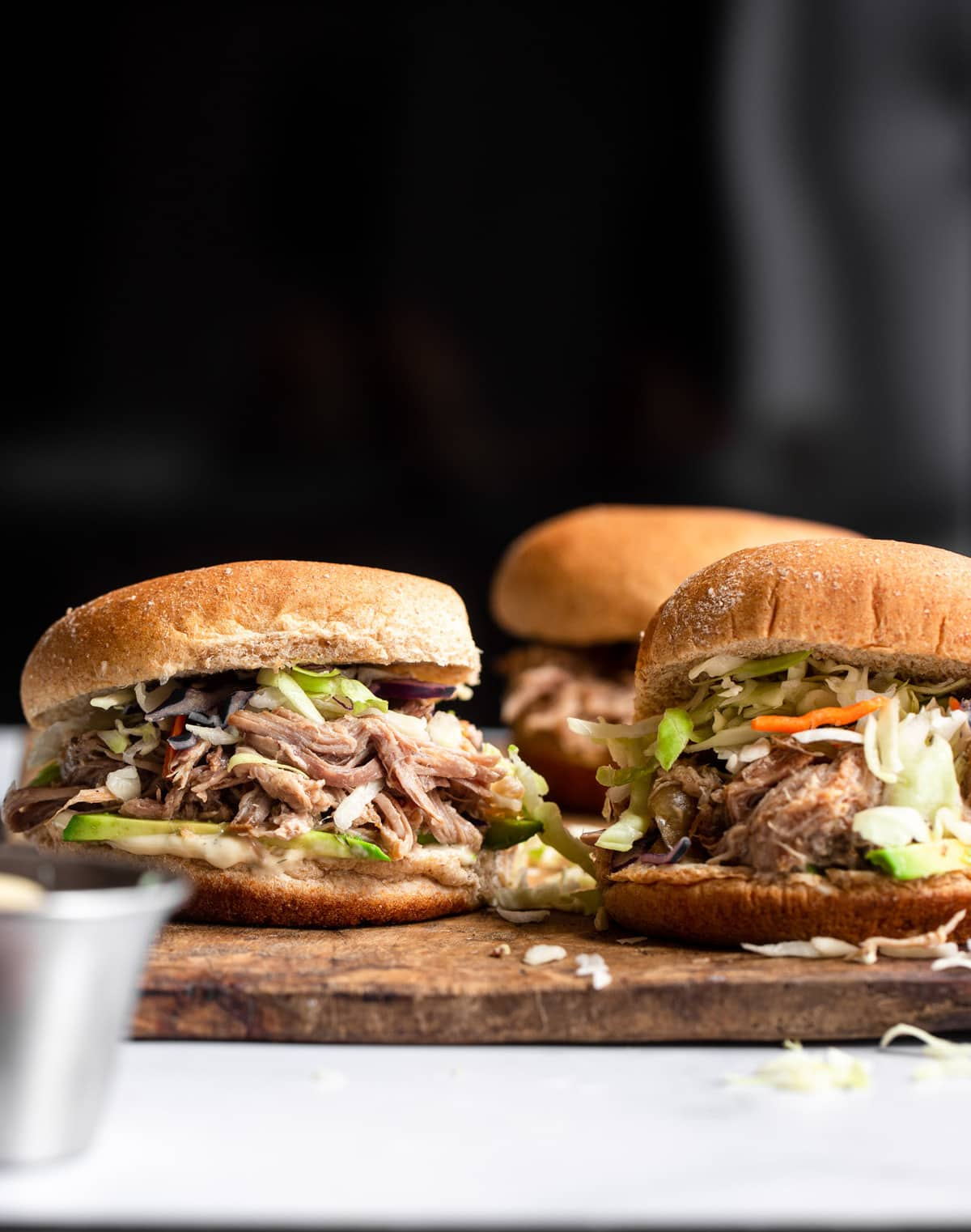 Keto pulled pork sandwiches on a cutting board with black background