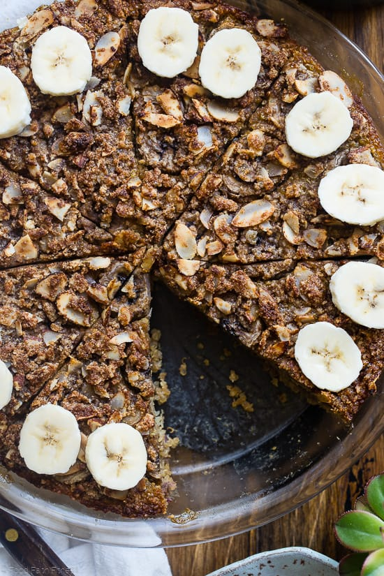 close up top view of quinoa breakfast bake in a pie dish with bananas on top
