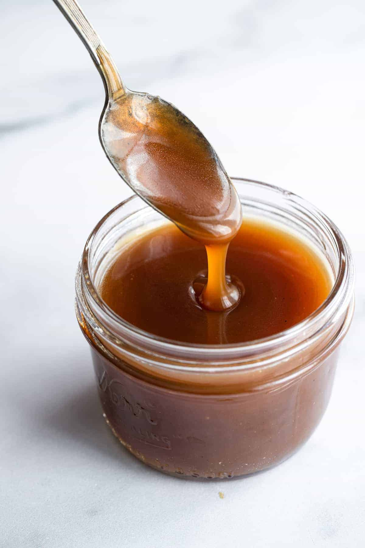 a spoon dipped in dairy free vegan caramel sauce