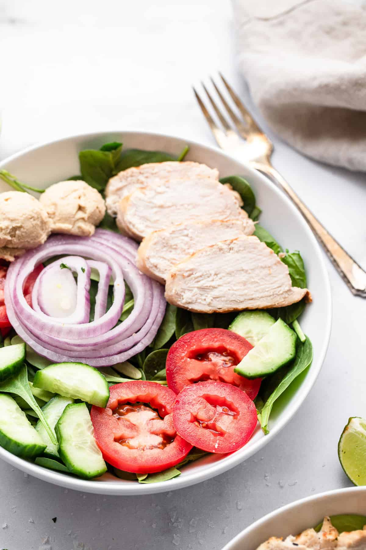 high protein hummus chicken salad in a bowl with tomtato