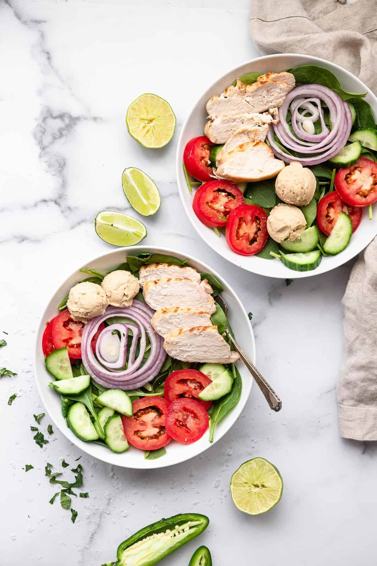 high protein hummus chicken salad in two bowls with limes