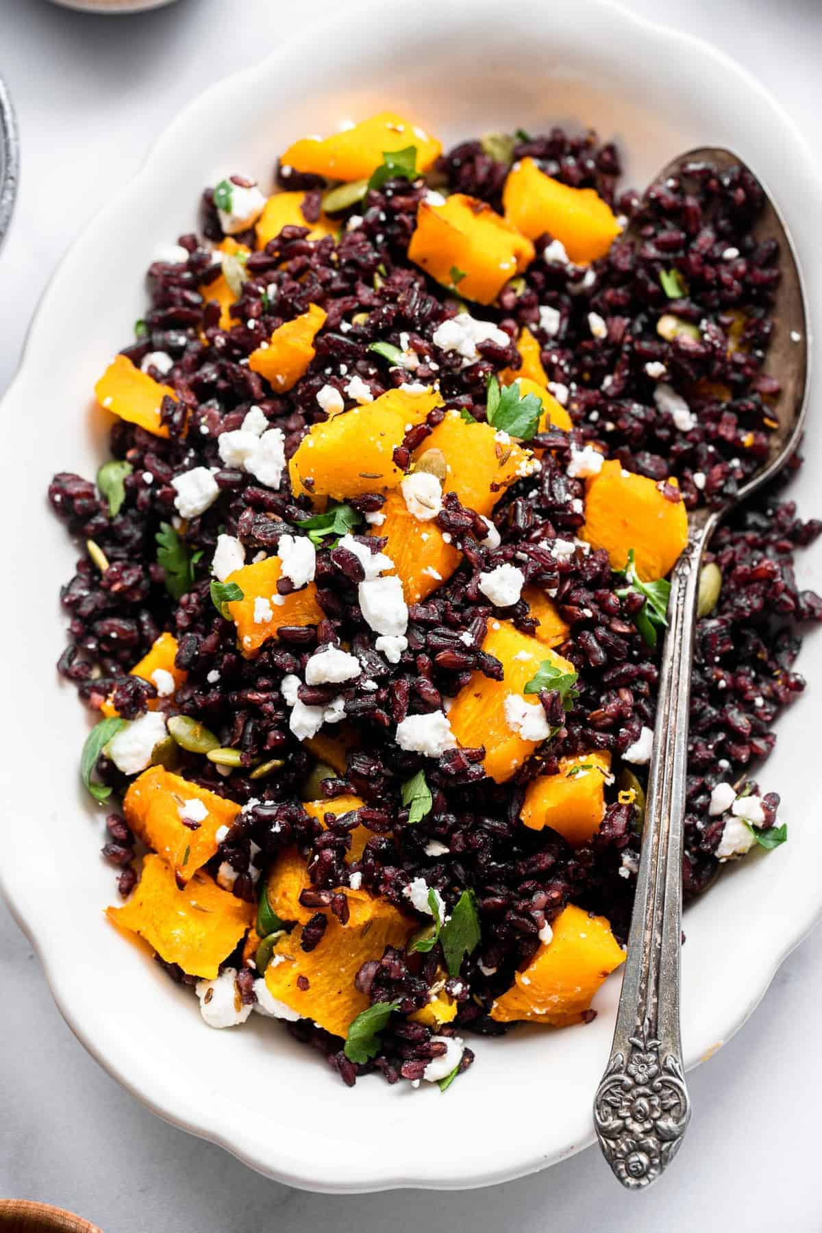 roasted pumpkin and black rice salad in a bowl with a spoon