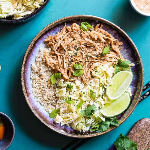 Slow Cooker Thai Peanut Chicken Quinoa Bowls -CREAMY crockpot Thai peanut chicken ismixed with quinoa and a spicy cabbage slaw to make a family friendly, gluten free and healthy meal! Theslow cooker does the work for you! | #Foodfaithfitness | #Glutenfree #Dairyfree #Healthy #Slowcooker #Crockpot