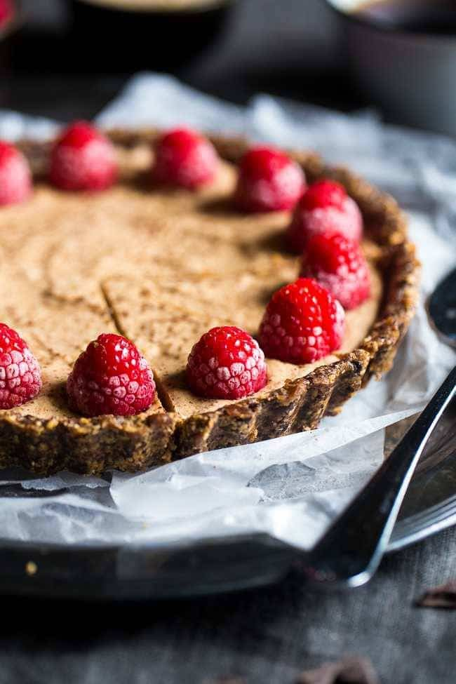 No-Bake Salted Chocolate Tart with Almond Cream - This easy tart is made from almonds and dates, then frozen and filled with almond cream. A healthy and gluten free dessert that can be made in advance! | Foodfaithfitness.com | @FoodFaithFit