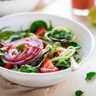 Vegan Spiralized Cucumber Salad with Chia Strawberry Vinaigrette - This healthy cucumber salad recipe is mixed with fresh herbs, strawberries and a homemade lime-strawberry vinaigrette. It's a fresh, paleo & vegan meal for only 230 calories! | Foodfaithfitness.com | @FoodFaithFit