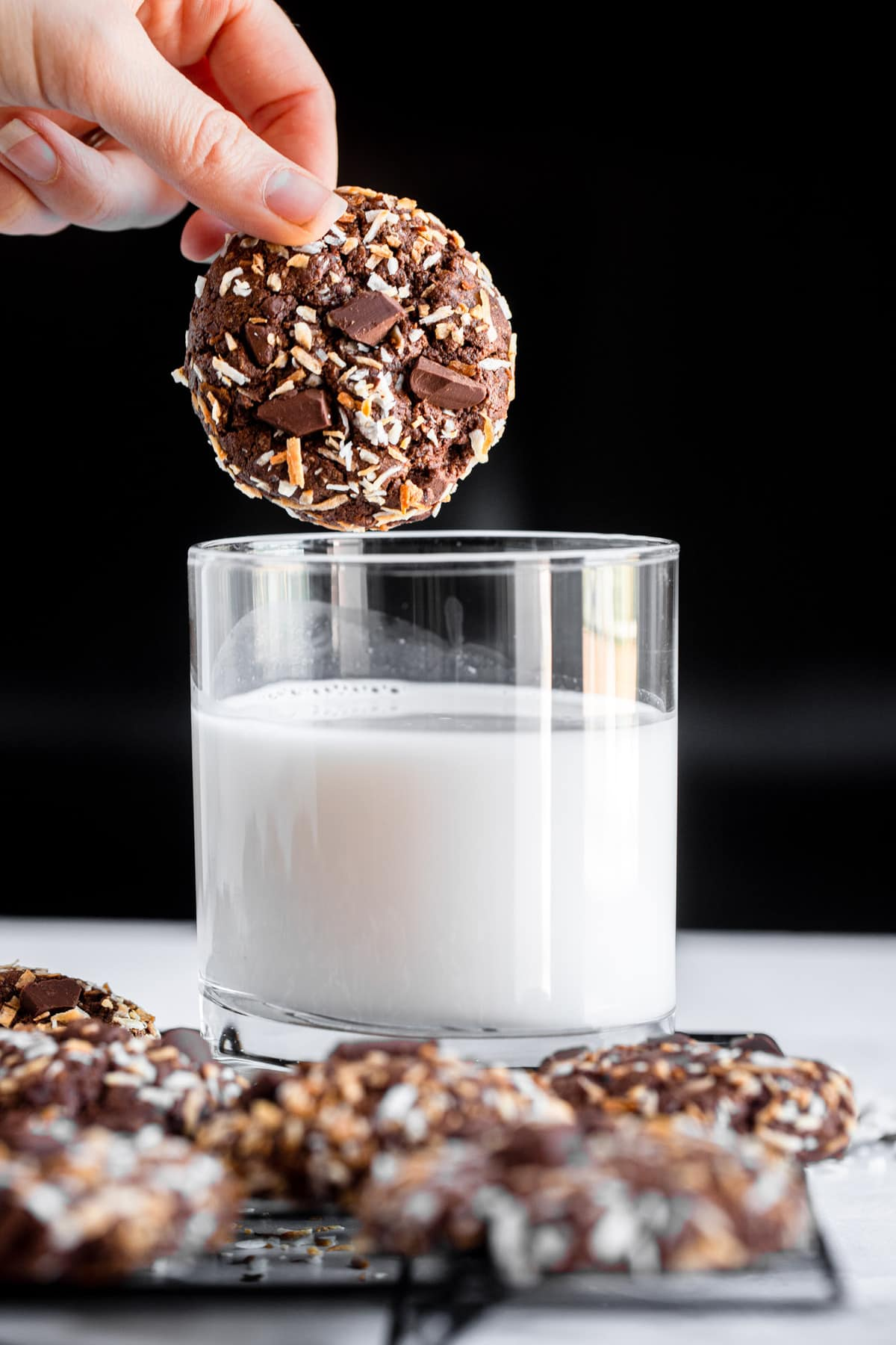 quinoa cookie being dipped into a glass on milk