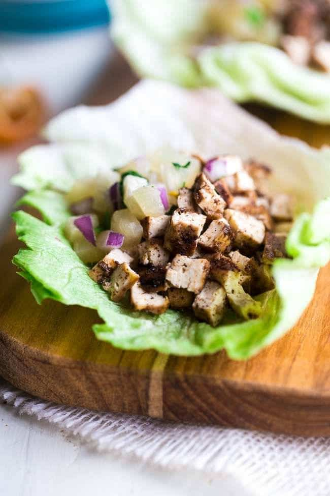 Easy Vegetarian Lettuce Wraps with Jerk Grilled Tofu - These lettuce wraps are piled with spicy-sweet and crispy grilled tofu and pineapple salsa. They're a quick and easy, healthy meal for Summer grilling or Meatless Monday! | #Foodfaithfitness | #Tofu #Vegan #Glutenfree #Vegetarian #Healthy