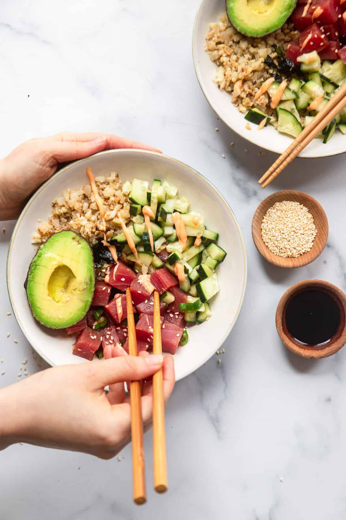 image of low carb poke bowl on a table being eaten with chopsticks