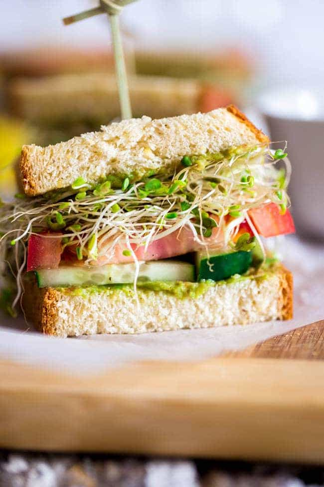 Mexican Avocado and Veggie Gluten Free Sandwiches - Slices of bread are layered with a creamy Mexican avocado spread, spicy sprouts, tomatoes and cucumbers. They're an easy, healthy meatless lunch option for under 250 calories! | Foodfaithfitness.com | @FoodFaithFit