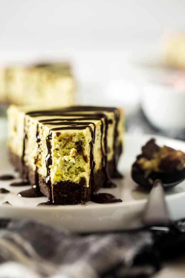 Gluten Free Brownie Bottomed Mint Chocolate Avocado Cheesecake - This creamy gluten free cheesecake uses avocado to make it naturally green. It has a rich brownie bottom crust and you'll never know it's secretly healthy! Perfect for Christmas! | Foodfaithfitness.com | @FoodFaithFit