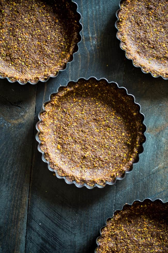 6 Ingredient Paleo and Vegan Raw Chocolate Pistachoo Tarts - This vegan tart is made with only 6 ingredients! It's a healthy, gluten free and paleo dessert that is easy to make! Perfect for Christmas!   Foodfaithfitness.com   @FoodFaithFit