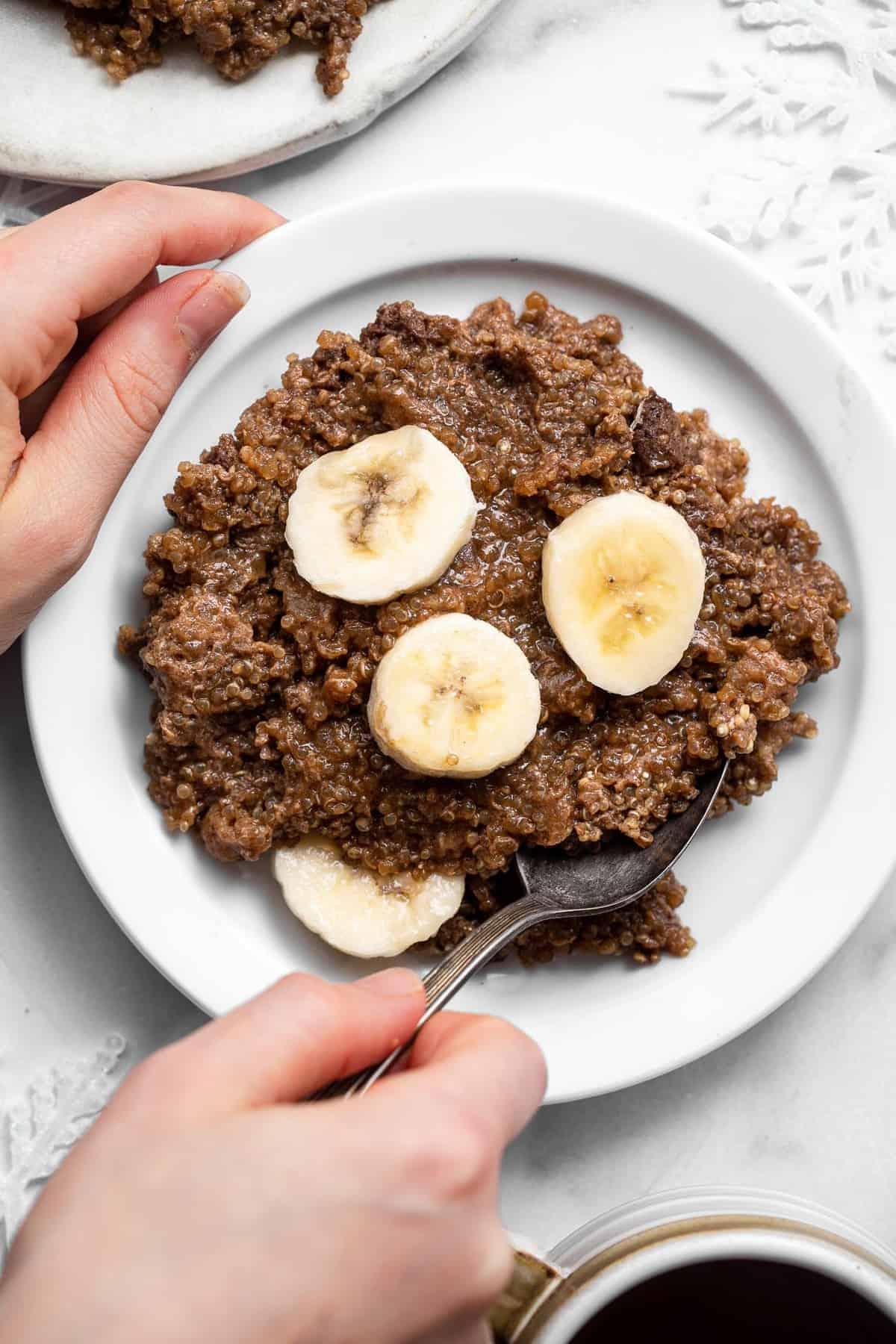 a hand holding a plate of quinoa breakfast bake