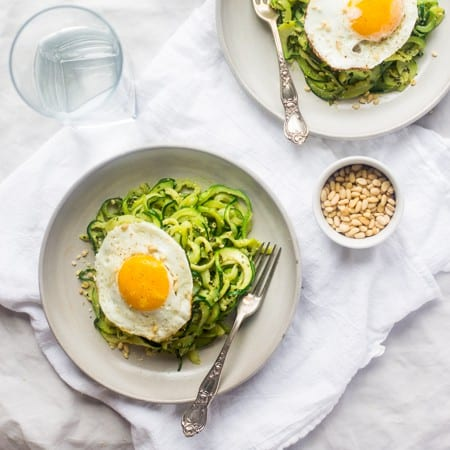 Paleo Zucchini Noodles with Everything Pesto and Fried Eggs - Zucchini noodles are mixed with creamy pesto and then topped with fried eggs. It's an easy, light and healthy, meatless weeknight dinner! | Foodfaithfitness.com | @FoodFaithFit