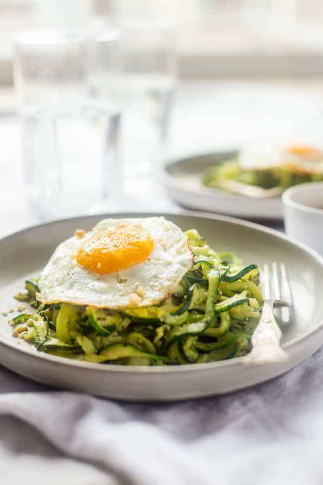 zucchini noodles with pesto and a fried egg on a gray plate