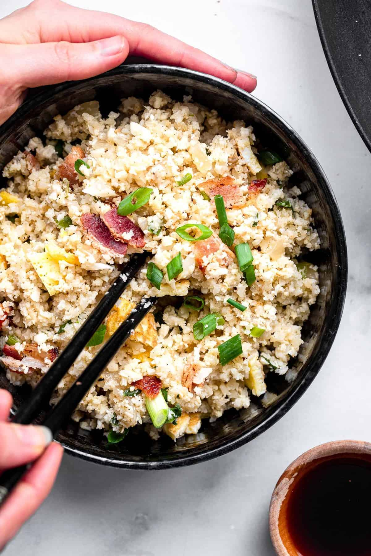 a bowl of whole30 paleo cauliflower fried rice with two hands holding it