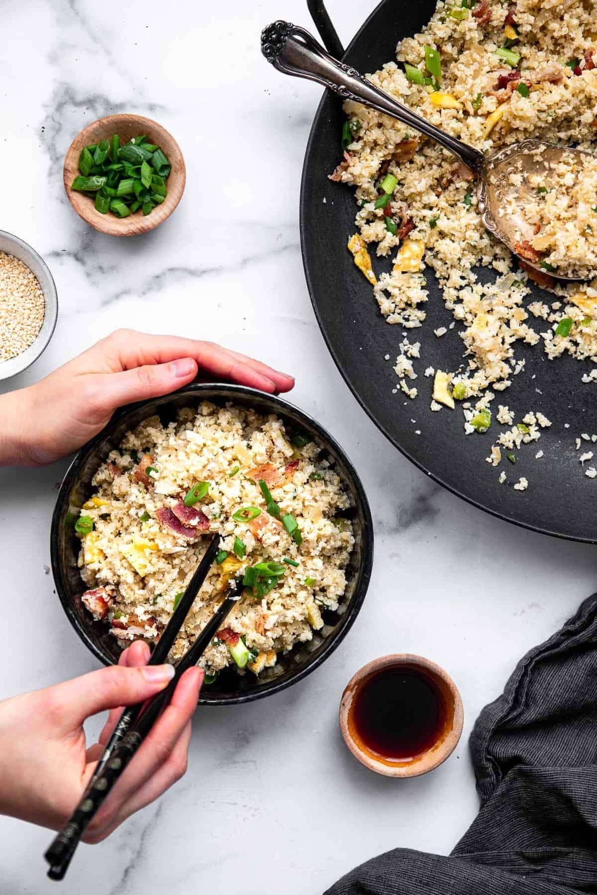 a bowl of keto fried rice with a hand holding chopsticks