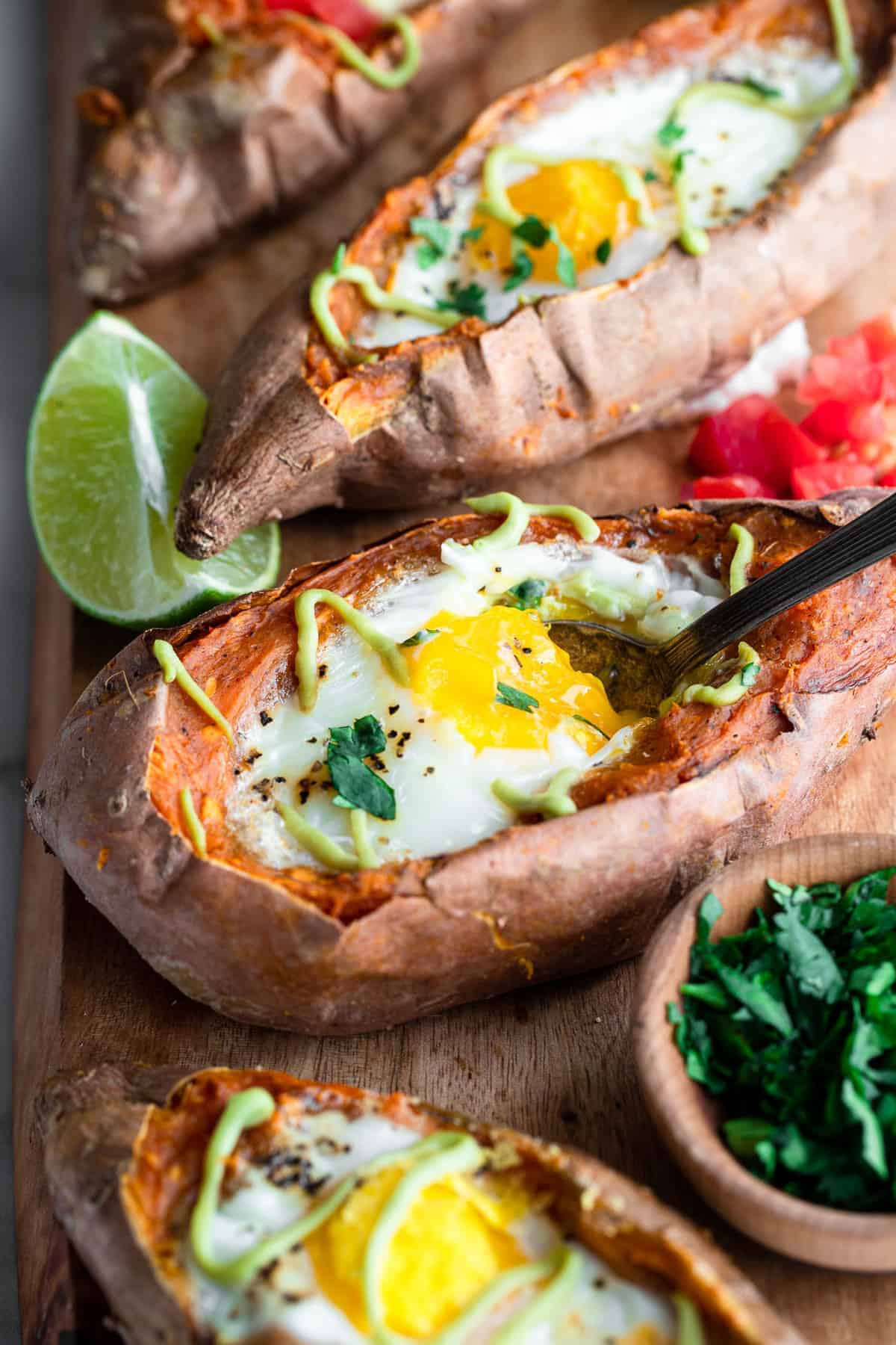 twice baked mexican sweet potatoes with eggs on a cutting board