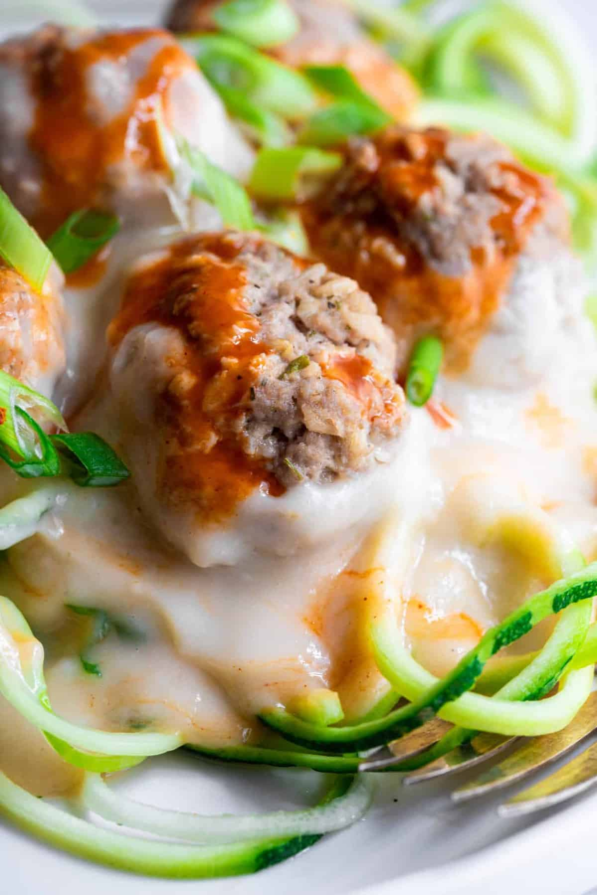 low carb buffalo chicken meatballs served over zucchini noodles