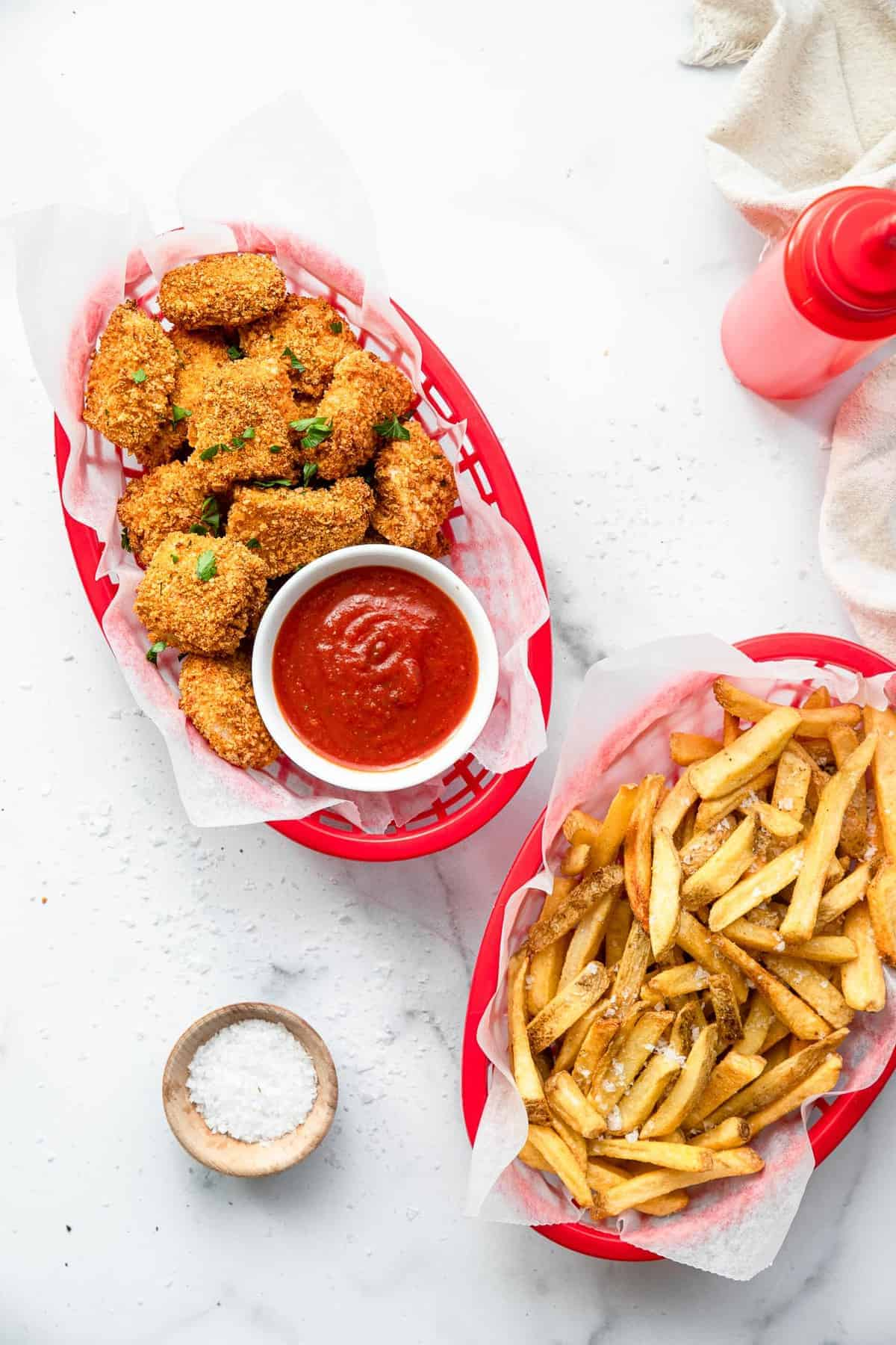 Air fryer chicken nuggets in a basket with fries on the side