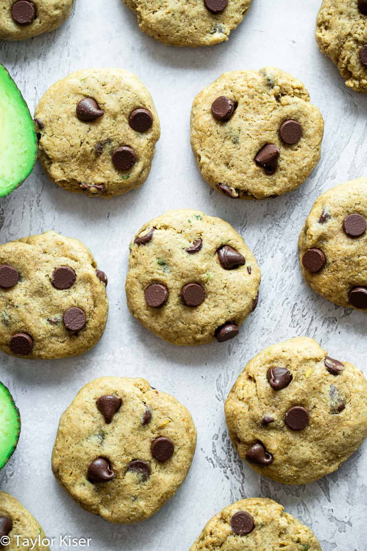 a bunch of Healthy Chocolate Chip Cookies next to raw avocados