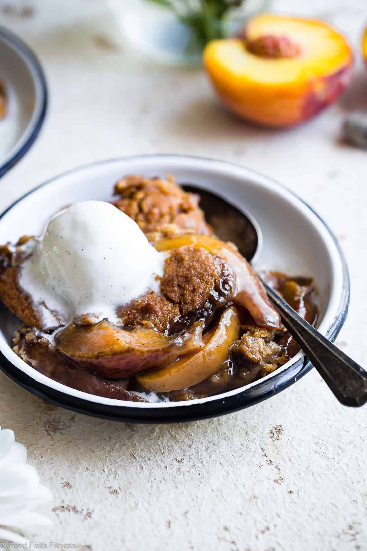 side view of paleo peach cobbler with ice cream on top in a bowl
