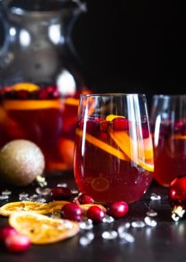 Sparkling Holiday Champagne Sangria - Full of tart cranberries and sweet oranges, this is aneasy, better-for-you cocktail that is perfect to serve a crowd this Holiday season! Fizzy, festive and tasty!   #Foodfaithfitness   #Glutenfree #Sangria #Dairyfree #Vegan #Champagne