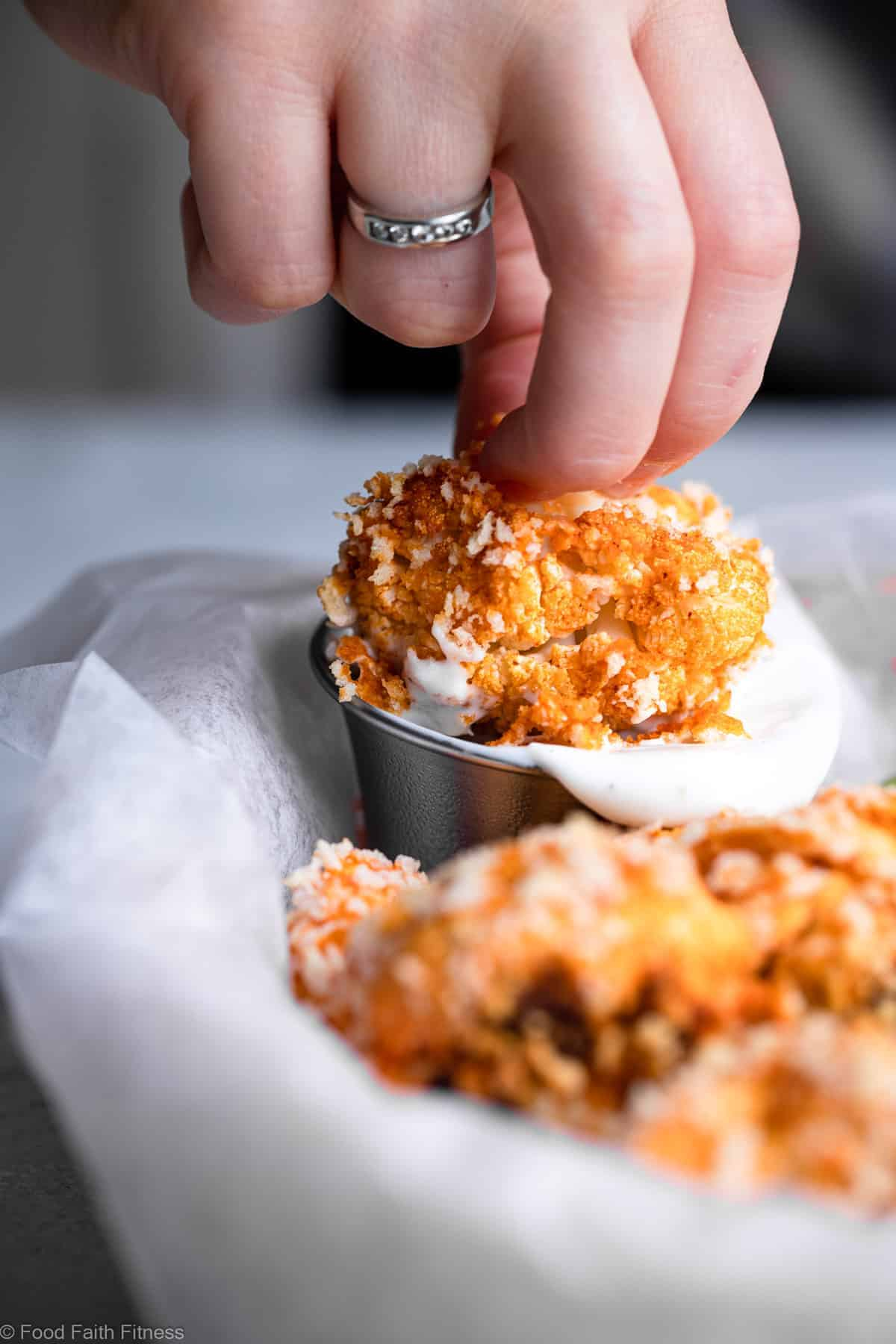 dipping fried cauliflower wings into sauce