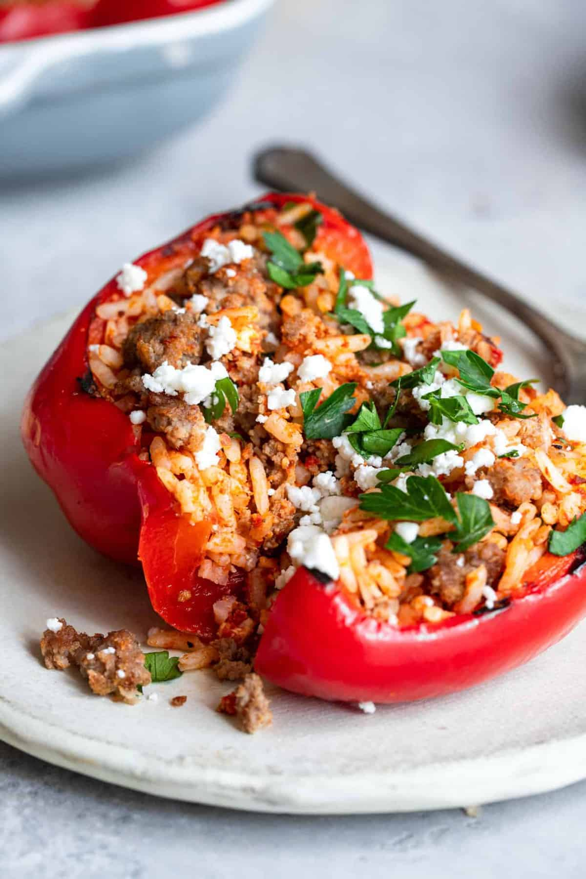 close up of grilled stuffed peppers on a plate cut open