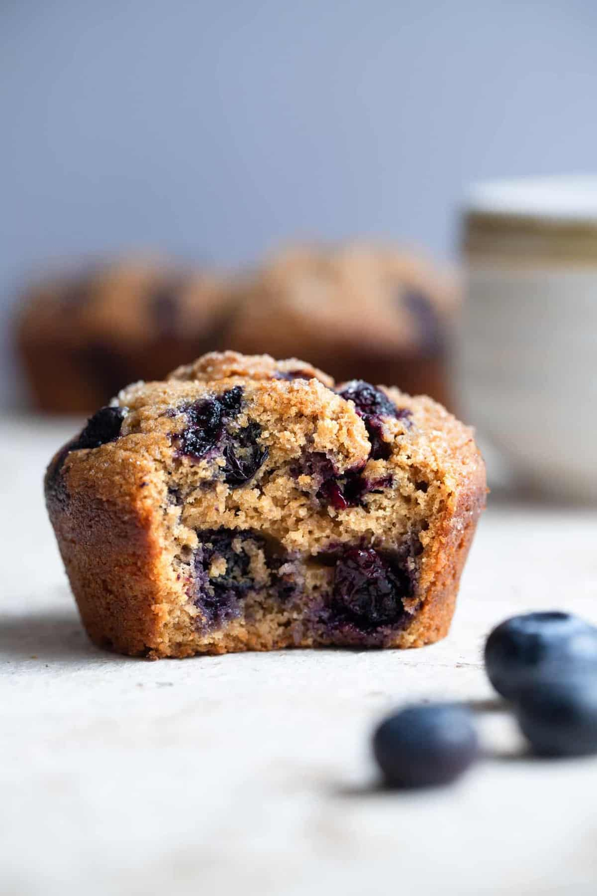 close up of whole wheat blueberry muffins with a bite taken out of one