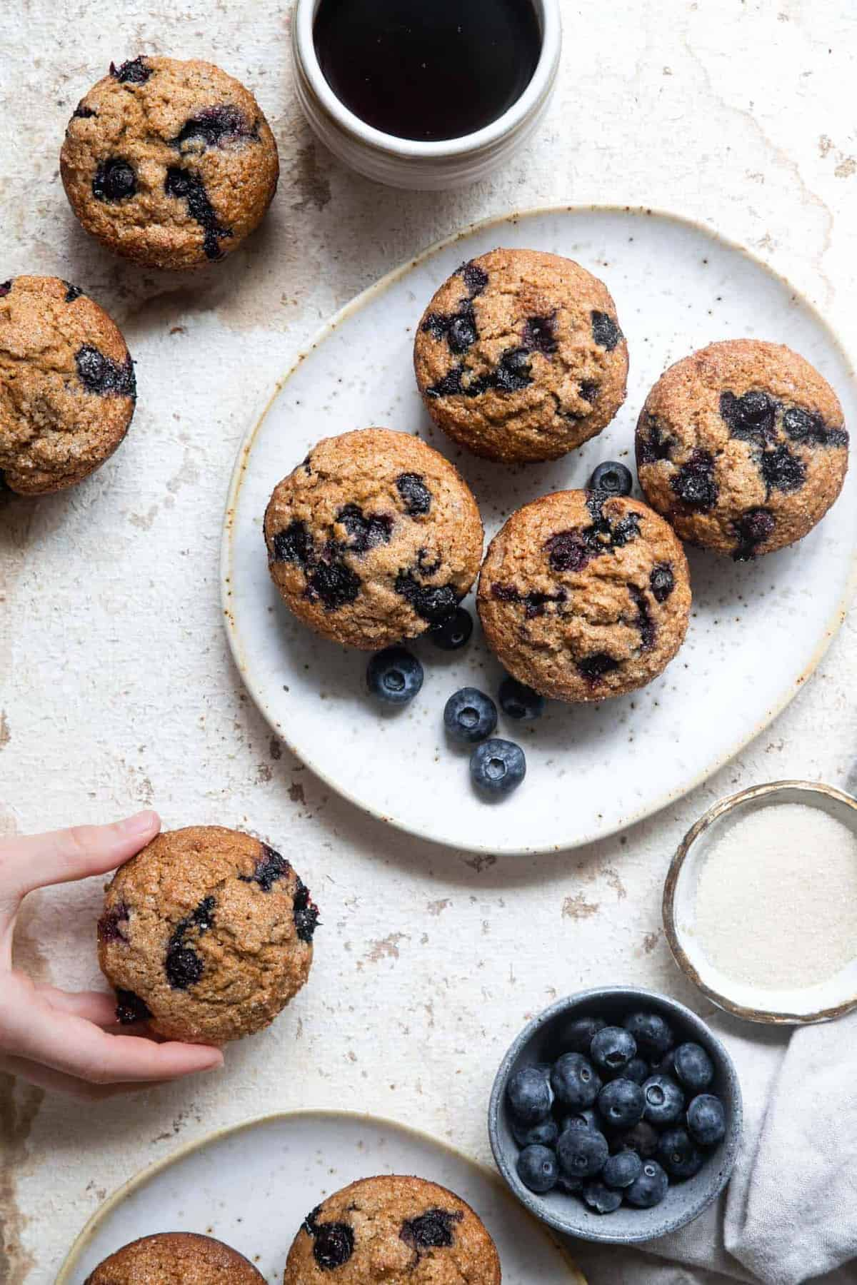 whole wheat blueberry muffins on a plate with a hand grabbing one