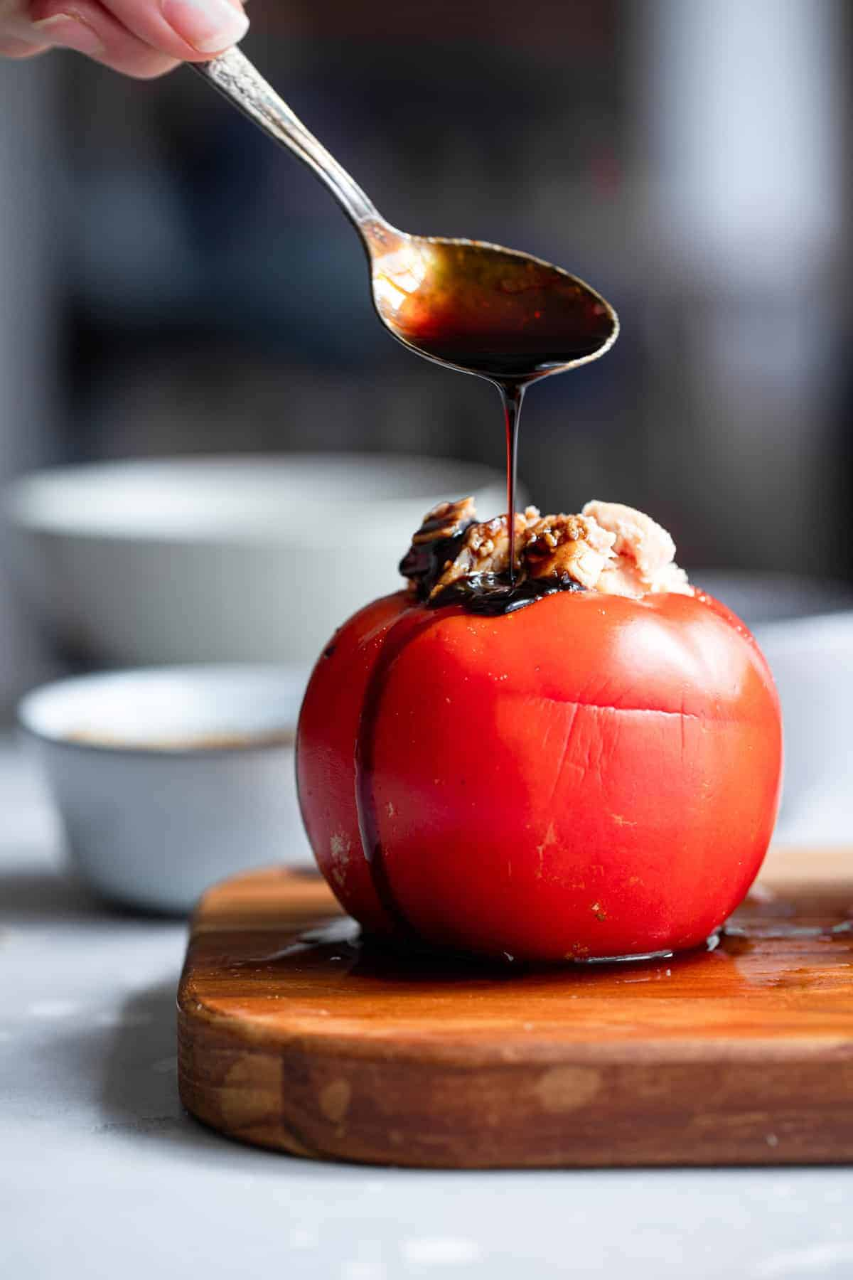 Pouring balsamic vinegar on tuna stuffed tomatoes