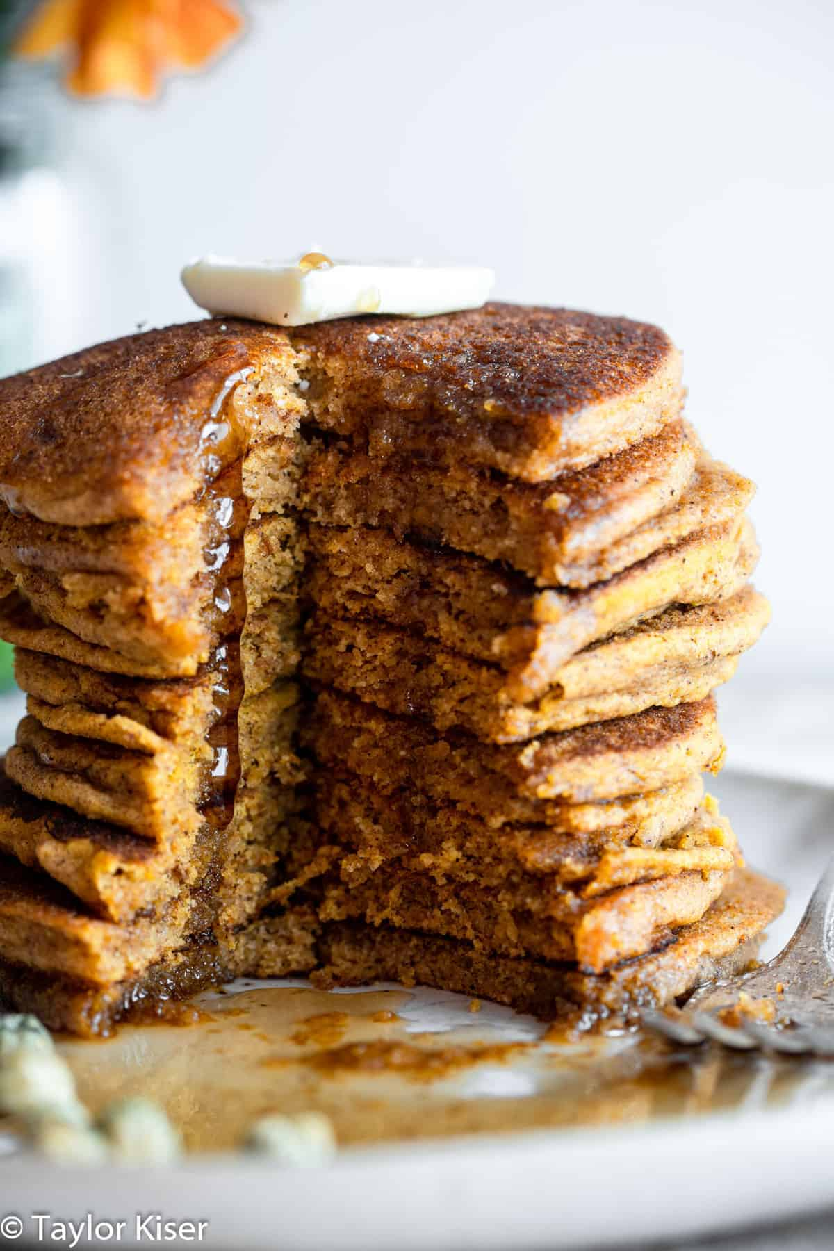 a stack of whole wheat healthy pumpkin pancakes with a cut down the middle