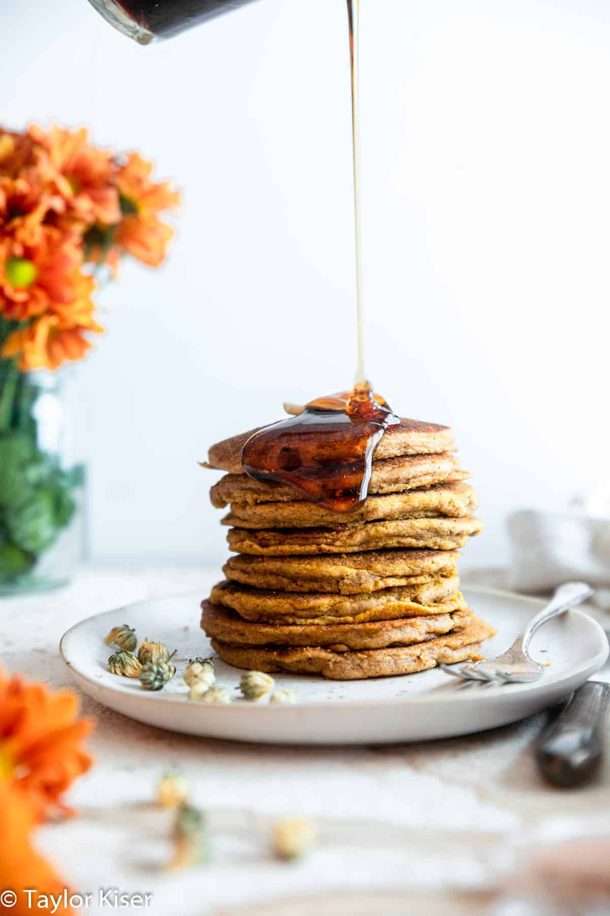 whole wheat pumpkin pancakes with syrup drizzling on them