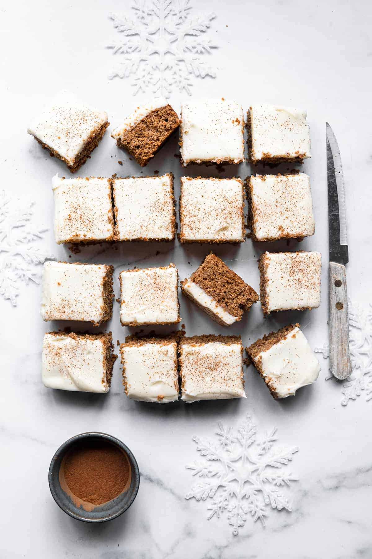 gluten free gingerbread cake bars sliced into squares with a knife beside them