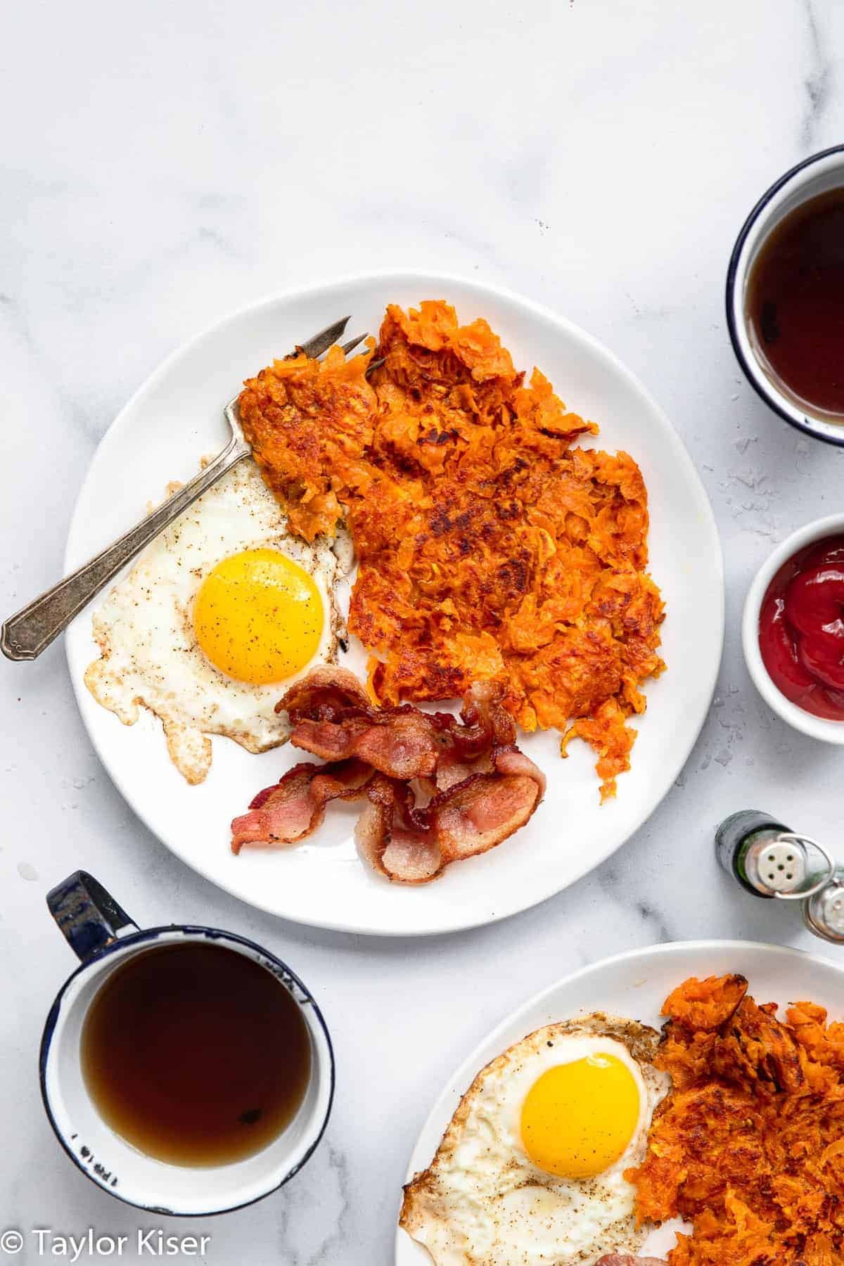 sweet potato hash browns on a plate with bacon and eggs