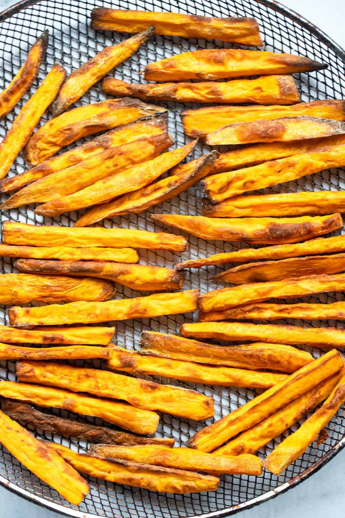 air fried sweet potato fries on a mesh basket