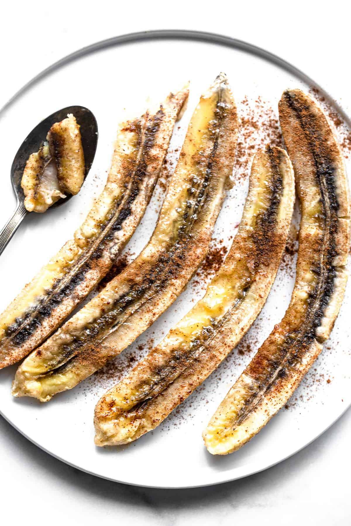 4 baked bananas on a plate with cinnamon on top
