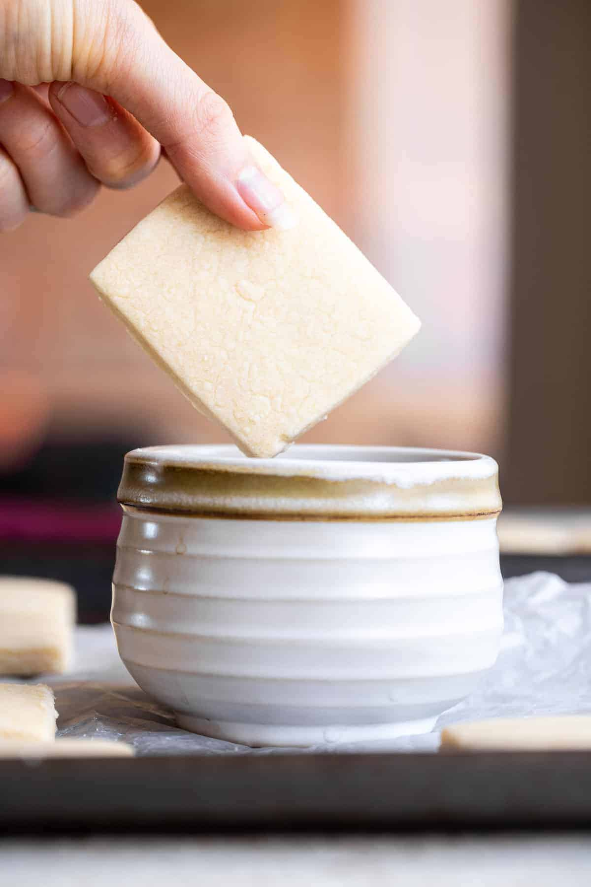Vegan butter cookies being dipped into a cup of coffee