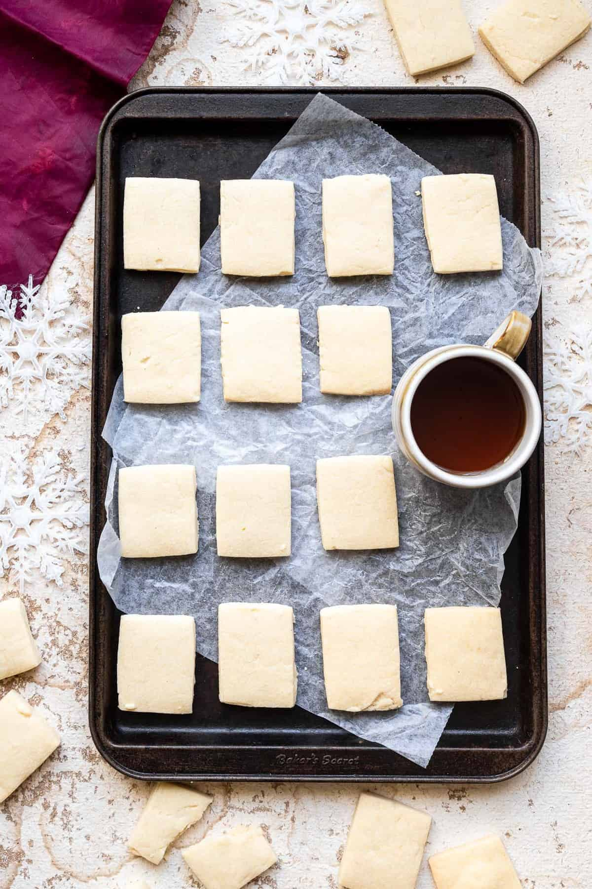 vegan shortbread cookies on a cookie sheet with a cup of coffee