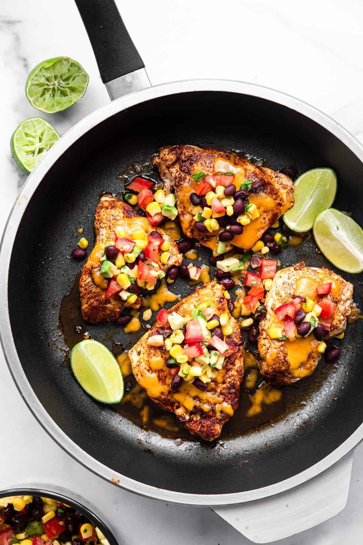 santa fe chicken in a skillet with cheese and black bean salsa