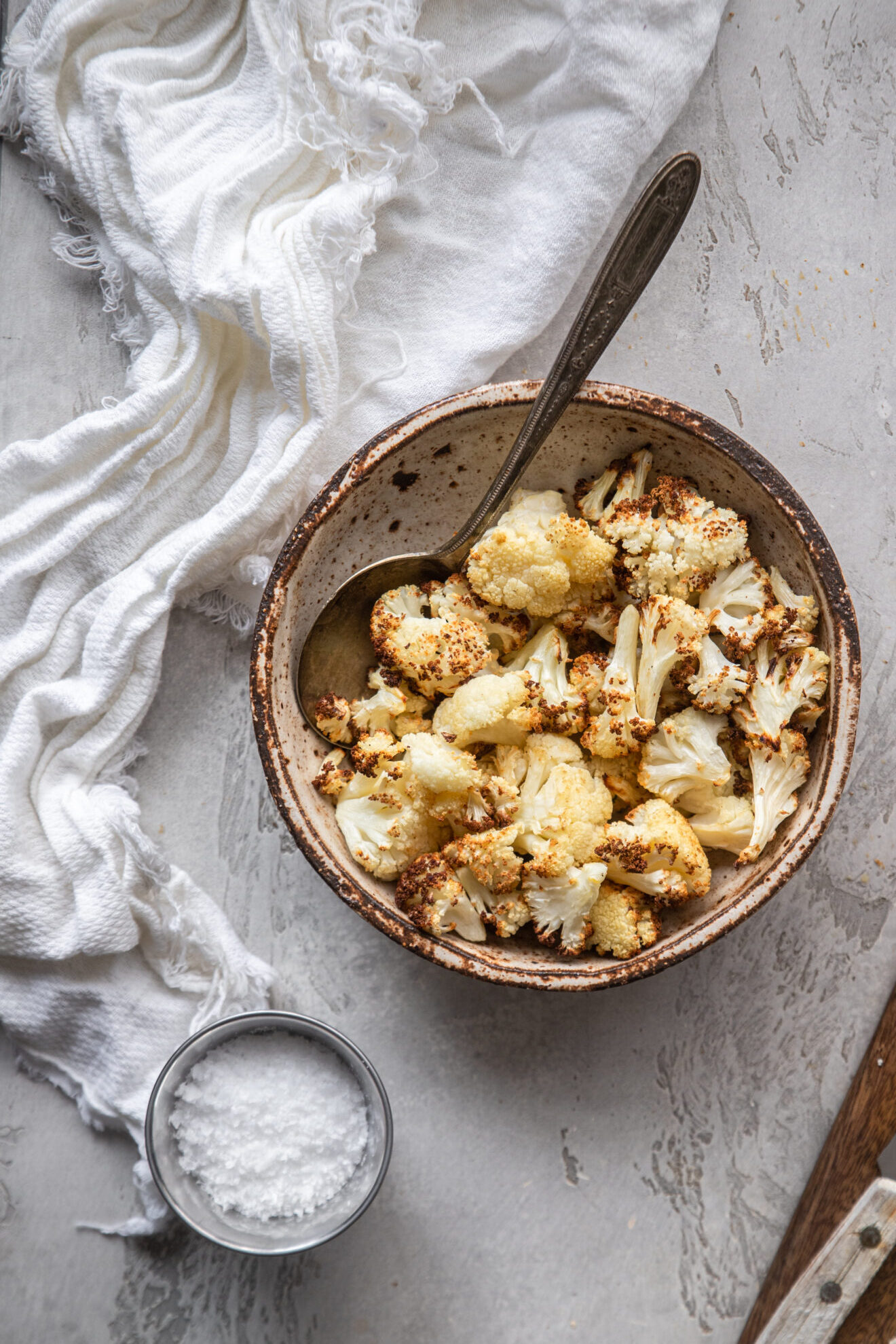 air fryer cauliflower in small bowl with spoon