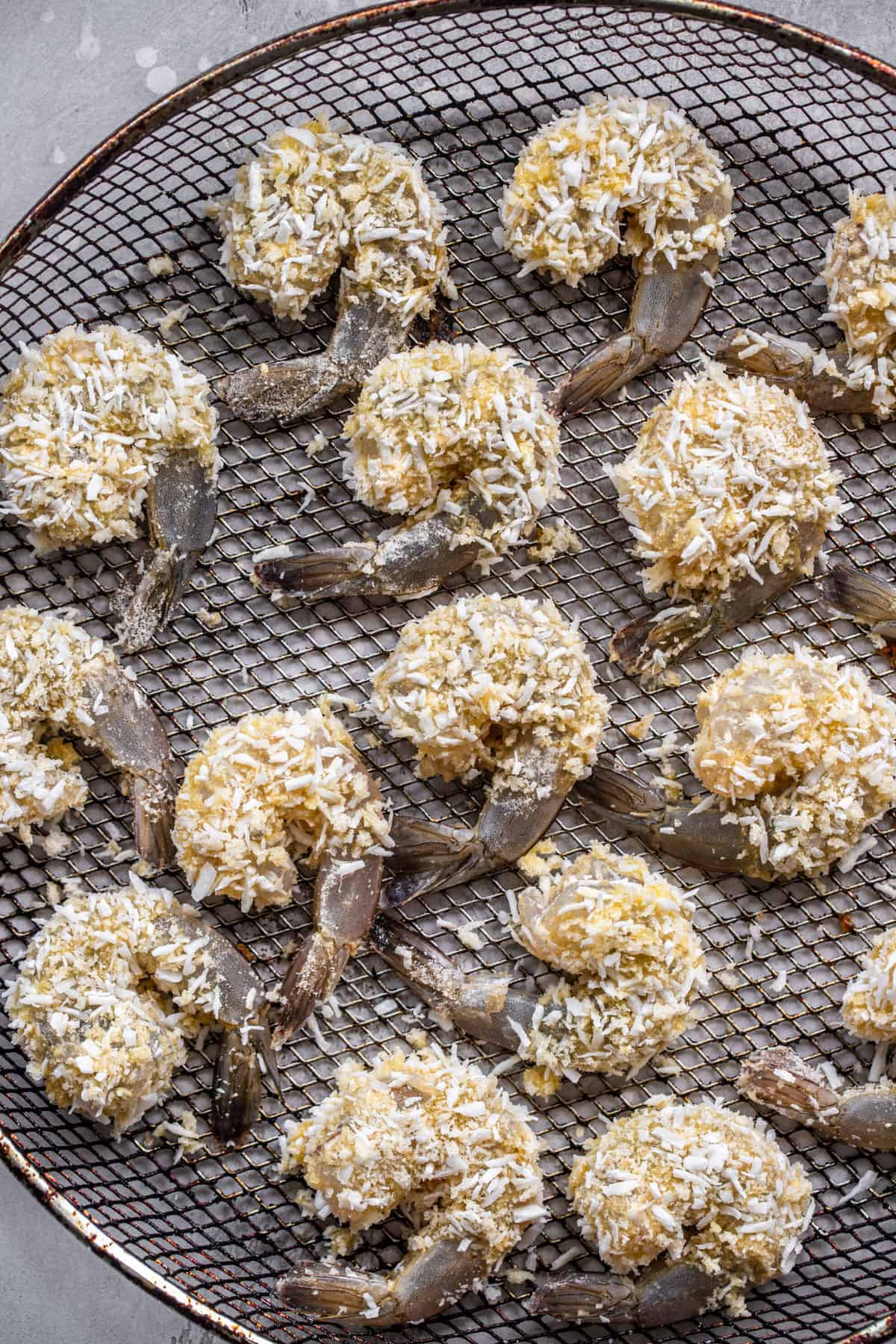Air fryer panko shrimp before being cooked on a mesh plate