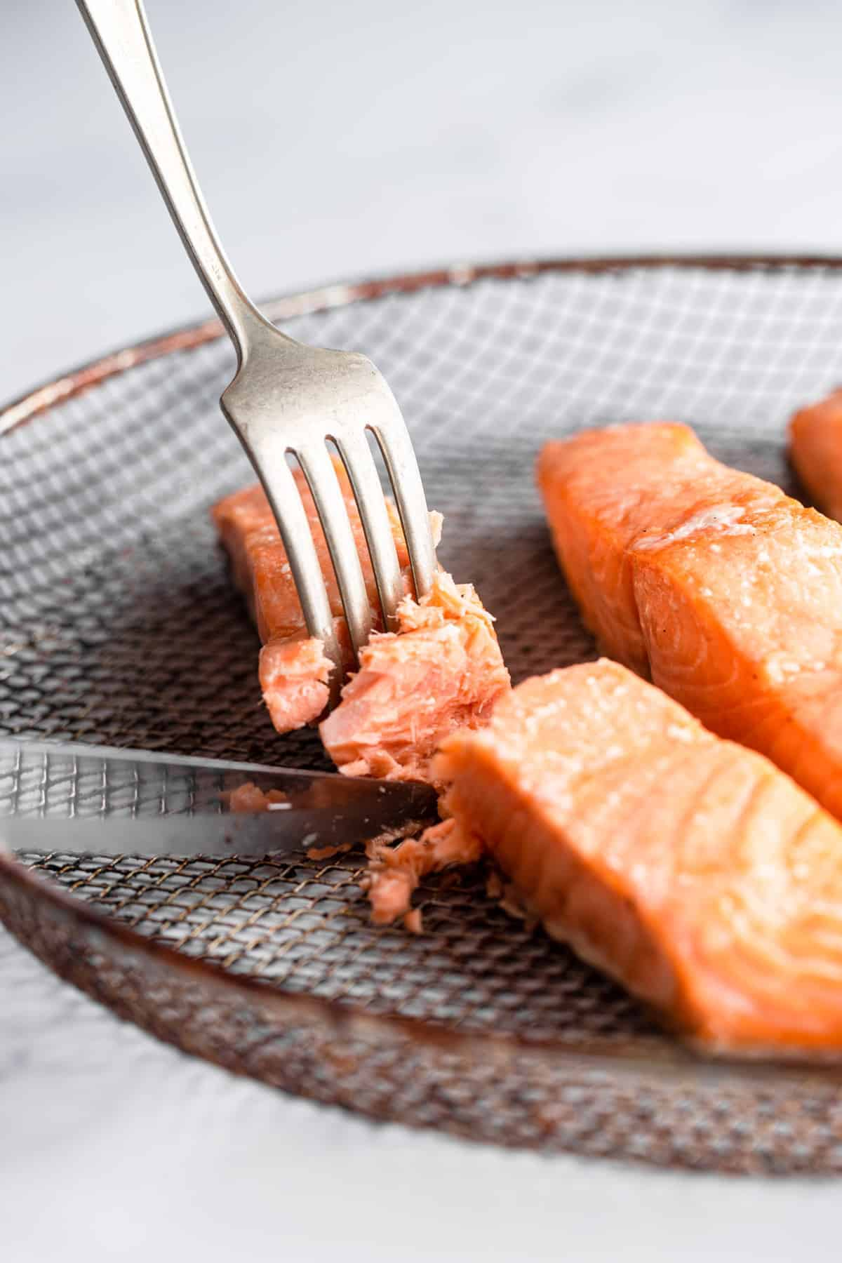 air fryer salmon cooked on a mesh plate with fork and knife