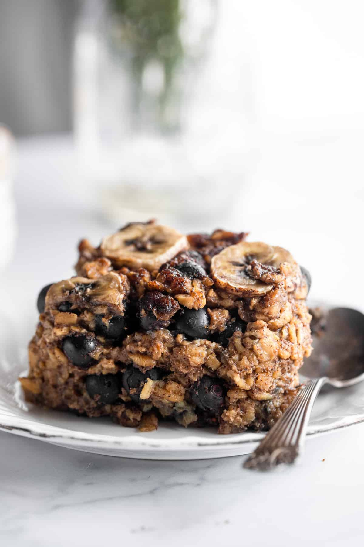 Blueberry Banana Baked Oatmeal on a small plate with a spoon