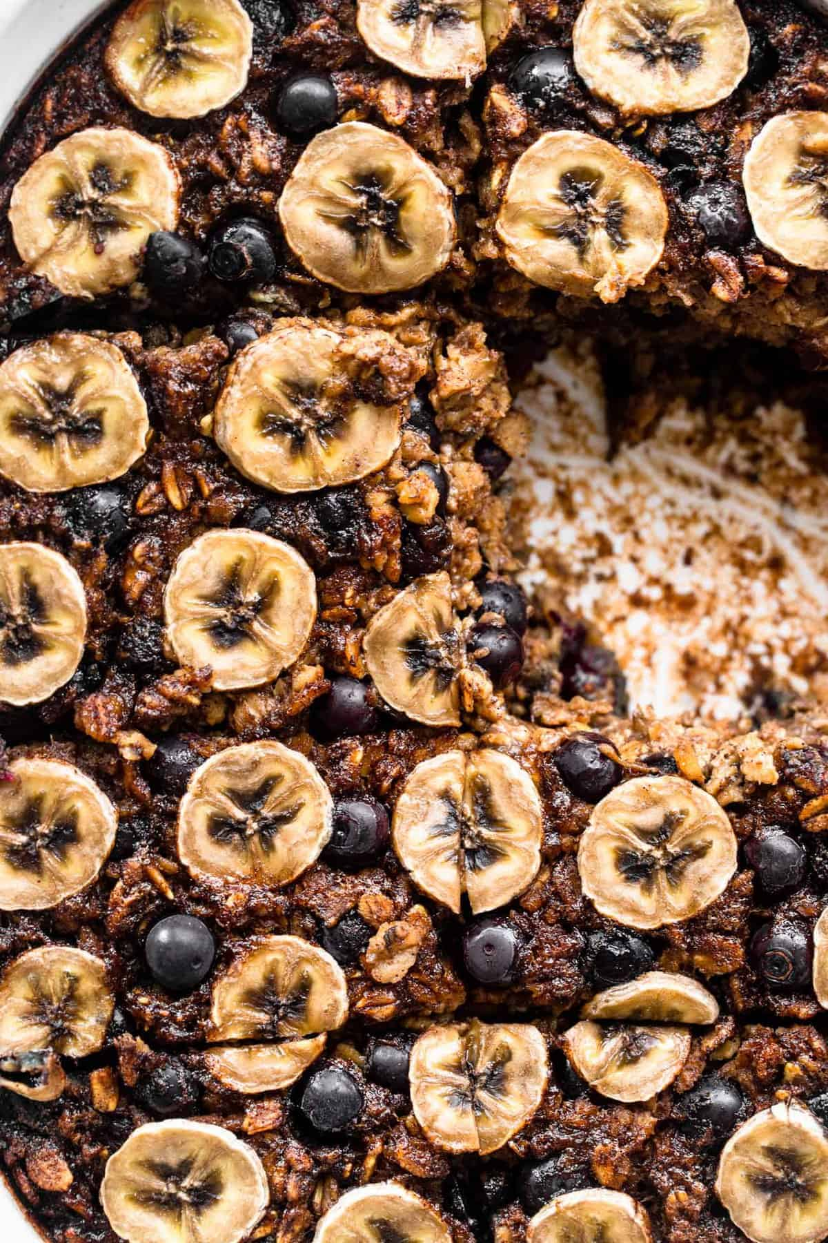 Baked oatmeal with blueberries and banana in a baking dish with slice missing