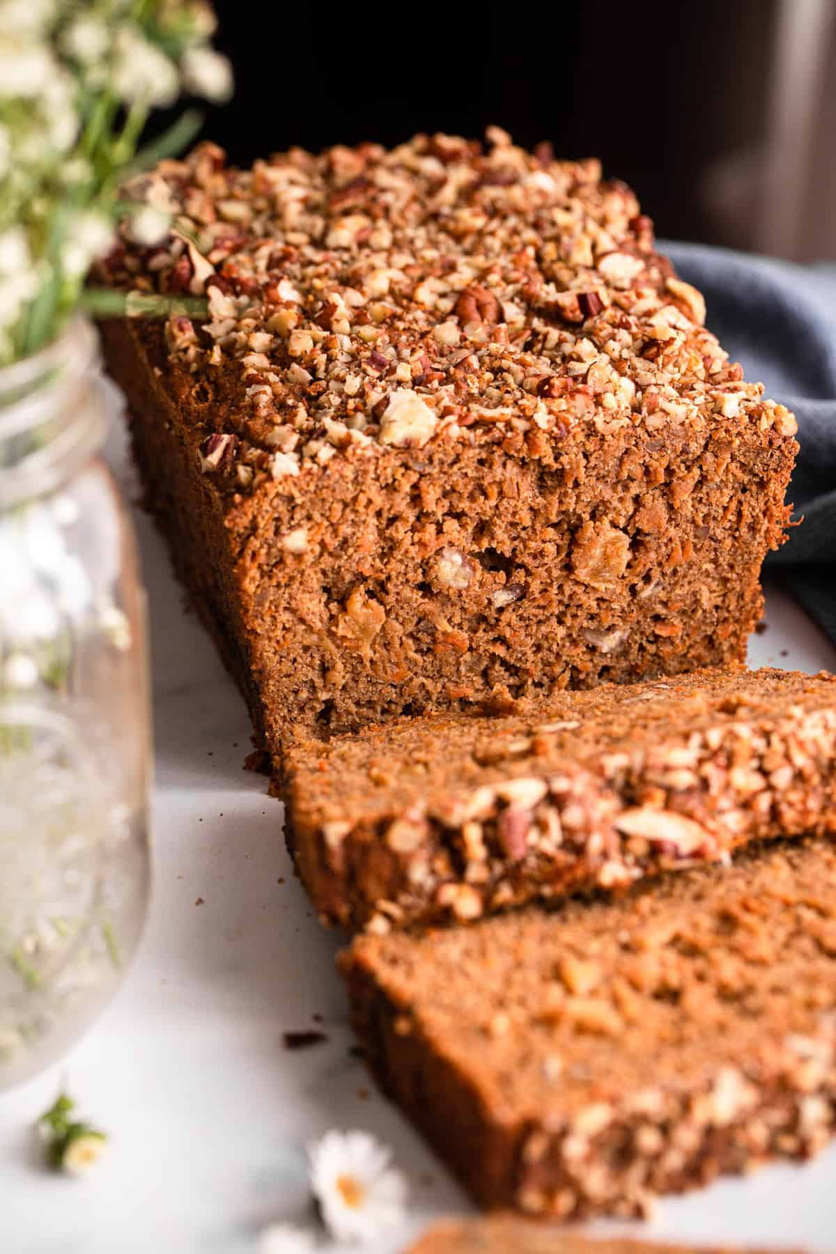 Healthy Carrot Bread on a table with napkin and flowers